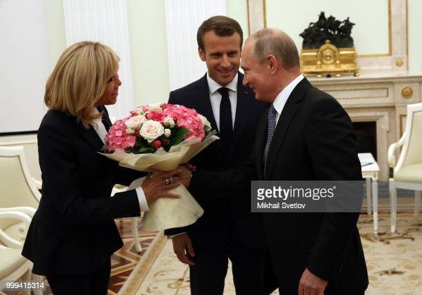 Russian President Vladimir Putin greets French President Emmanuel Macron and his wife Brigitte Macron during their talks at the Kremlin in Moscow...