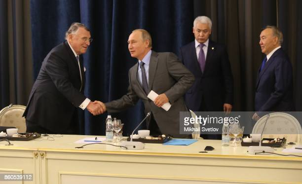 Russian President Vladimir Putin greets German businessman CEO of TUI AG Klaus Mangold as Kazakh President Nursultan Nazarbayev looks on during their...