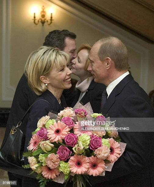Russian President Vladimir Putin greets German Chancellor Gerhard Schroeder's wife Doris as Gerhard Schroeder kisses Putin's wife Lyudmila in the...