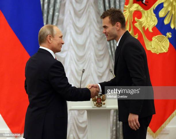 Russian President Vladimir Putin greets goalkeeper Igor Akinfeev during the awarding ceremony at the Kremlin or July 28 2018 in Moscow Russia...