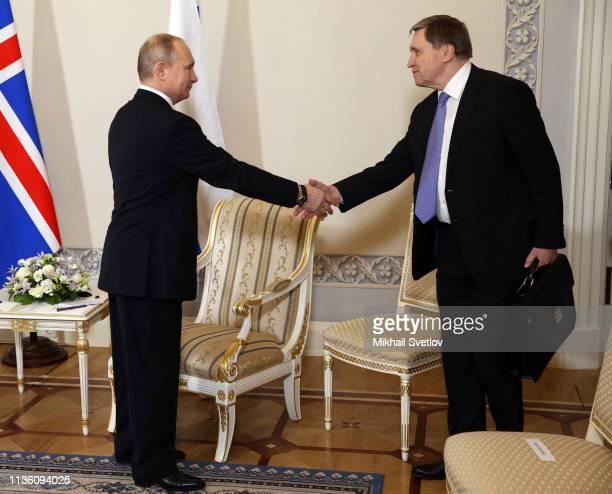 Russian President Vladimir Putin greets his aide Yuri Ushakov prior to his talks with Iceland's President Gudni Thorlasius Johannesson at Konstantin...