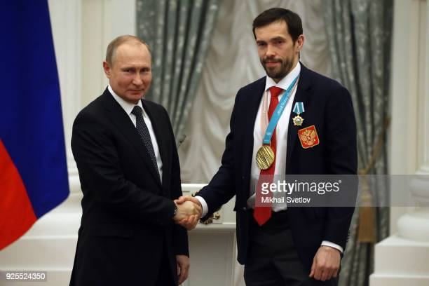 Russian President Vladimir Putin greets ice hockey player Pavel Datsyuk during his meeting with athlets from Russia who took part in the 2018 Winter...