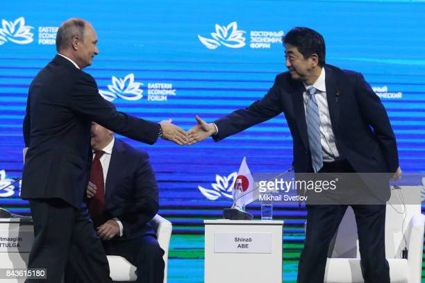 Russian President Vladimir Putin greets Japanese Prime Minister Shinzo Abe at the plenary session of the Eastern Economic Forum on September 7 2017...