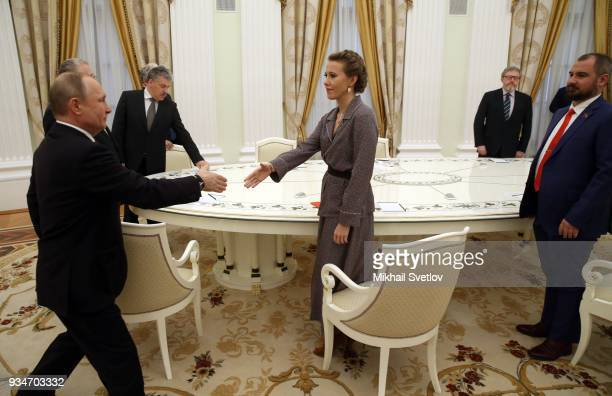 Russian President Vladimir Putin greets liberal candidate Ksenia Sobchak as Communists of Russia Party Maxim Suraykin and Yabloko party foiunder...