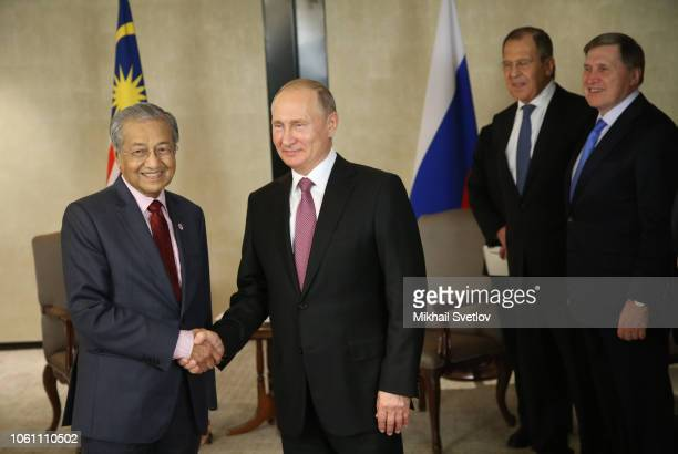 Russian President Vladimir Putin greets Malaysian Prime Minister Mahathir Mohamad as Russian Foreign Minister Sergei Lavrov and Presidential Aide...