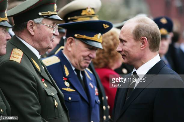 Russian President Vladimir Putin greets members of the military as he attends a wreath-laying ceremony at the Tomb of the Unkown Soldier near the...