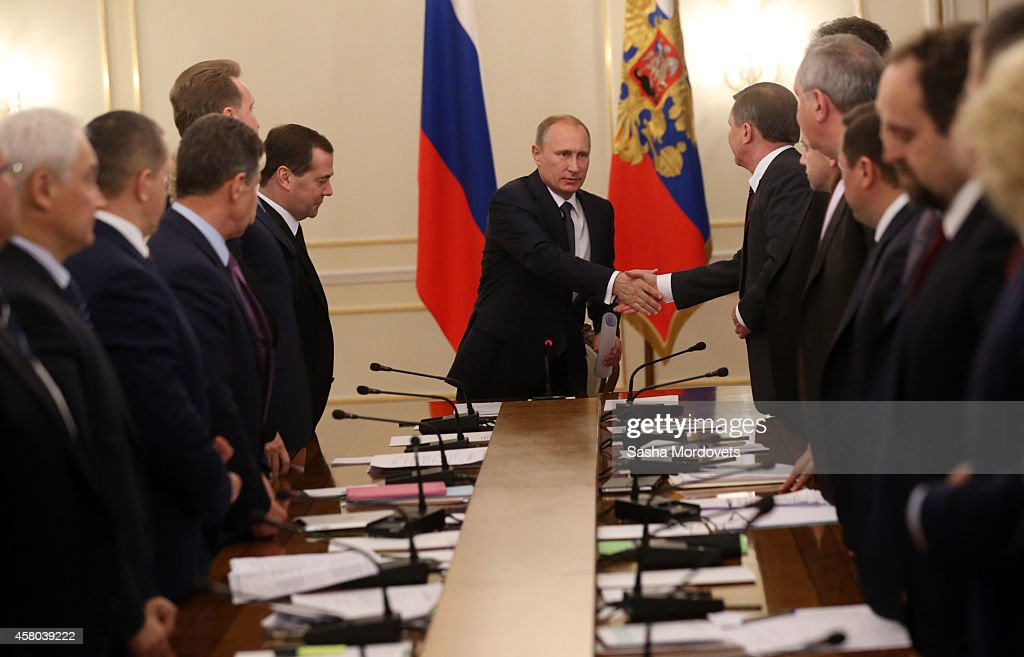 Russian President Vladimir Putin (C) greets Presidential Chief of Staff Sergei Ivanov (R) during a weekly meeting with ministers of the government at the Novo Ogaryovo state residence October 29, 2014 in Moscow Russia.