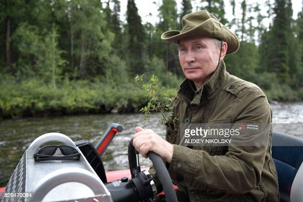 Russian President Vladimir Putin guides a boat during his vacation in the remote Tuva region in southern Siberia The picture taken between August 1...
