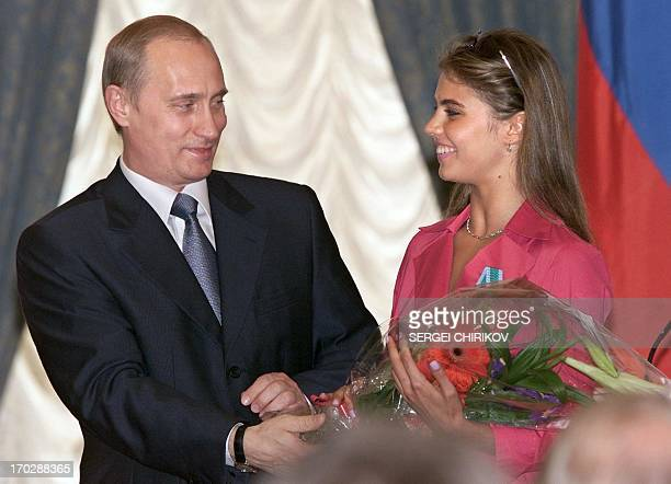 Russian President Vladimir Putin hands flowers to Alina Kabayeva, Russian rhytmic gymnastics star and Olympic prize winner, after awarding her with...