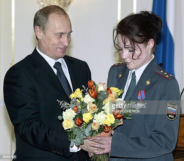 Russian President Vladimir Putin hands flowers to police Captain Yelena Nikitina from StPetersburg after decorating her with a medal 'For Distinction...