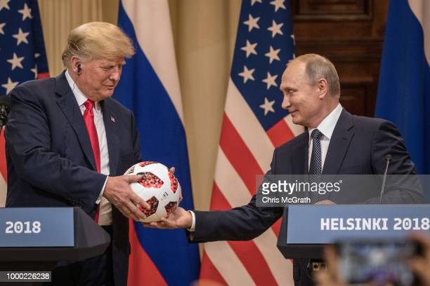 Russian President Vladimir Putin hands US President Donald Trump a World Cup football during a joint press conference after their summit on July 16...