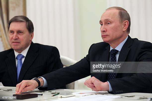 Russian President Vladimir Putin his advisor Yuri Ushakov attend a meeting with UN Secretary-General Ban Ki-moon in the Kremlin on March 20, 2014 in...