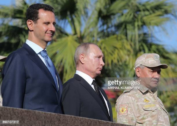 Russian President Vladimir Putin his Syrian counterpart Bashar alAssad and Russian Defence Minister Sergei Shoigu inspect a military parade during...