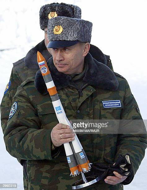 Russian President Vladimir Putin holds 18 February 2004 a replica of the Molnia spacecraft which was successfully launched from the Artic cosmodrome...