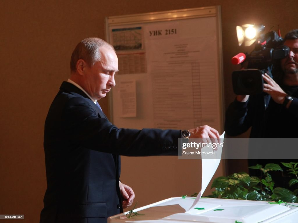 Russian President Vladimir Putin holds a ballot paper for mayoral elections at the polling station on September 08, 2013 in Moscow, Russia. Opposition leader Alexey Navalny, one of Putin's most vocal critics is a candidate for mayor in Moscow.