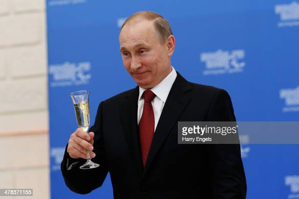 Russian President Vladimir Putin holds a glass of champagne during a lunch hosted by the office of the Russian President Vladimir Putin for the...