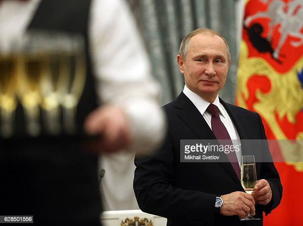 Russian President Vladimir Putin holds a glass of champagne during the awarding ceremony for Human Rights and Civil Society activists at the Grand...