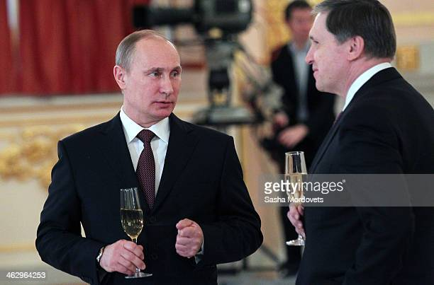 Russian President Vladimir Putin holds a glass of champaigne as his advisor Yuri Ushakov looks on during a presentation of credentials for new...