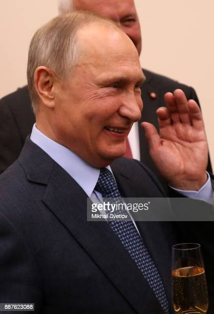 Russian President Vladimir Putin holds a glass of champaigne during a reception with the Rostec State Corporation CEO and workers to celebrate the...