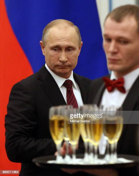 Russian President Vladimir Putin holds a glass of champaigne during an awarding cemeremony at the Kremlin in Moscow Russia December 18 2017 Vladimir...