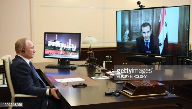 Russian President Vladimir Putin holds a meeting with his Syrian counterpart Bashar al-Assad via a video conference call at the Novo-Ogaryovo state...