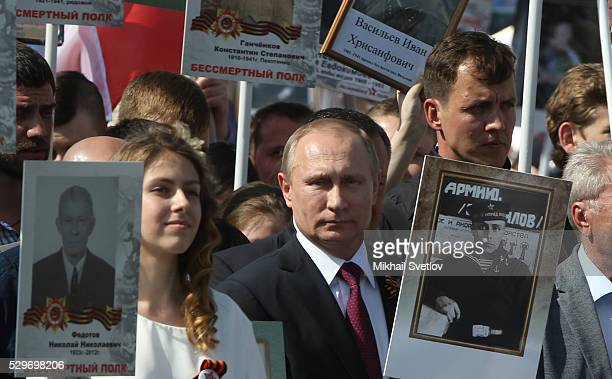 Russian President Vladimir Putin holds a photograph of his father in a naval uniform as he walks with people carrying portraits of relatives who...