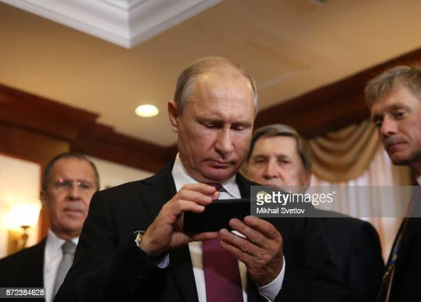 Russian President Vladimir Putin holds an iPhone as his spokesman Dmitry Peskov looks on prioir to a bilateral meeting with Philippines President...