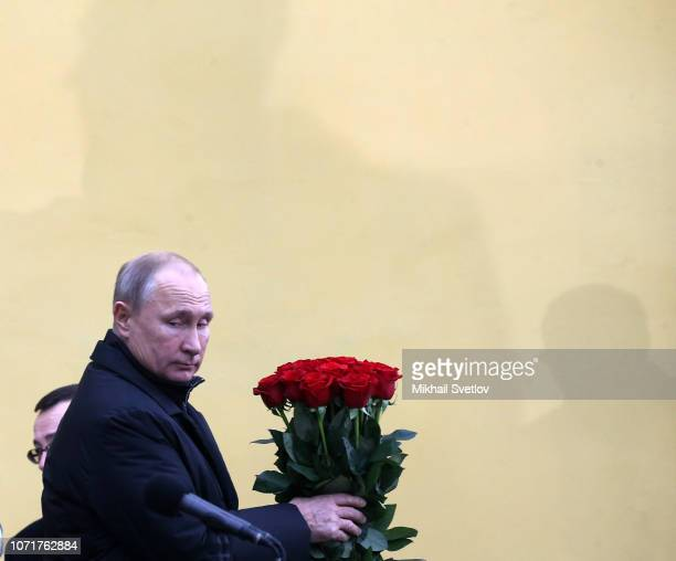 Russian President Vladimir Putin holds flowers during the opening ceremony of new monument to Soviet dissident and writer Alexander Solzhenitsyn in...