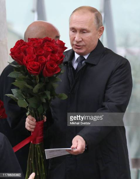 Russian President Vladimir Putin holds flowers during the openings of new monument to former Russian Prime Minister Yegeny Primakov at Smolenskaya...