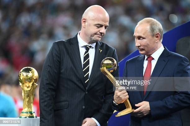 Russian President Vladimir Putin holds the adidas Golden Ball prize beside FIFA president Gianni Infantino during the trophy ceremony at the end of...