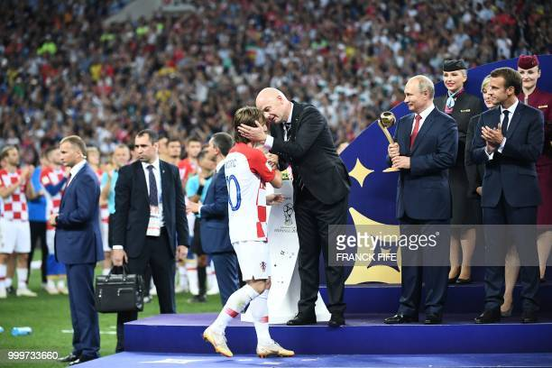 Russian President Vladimir Putin holds the adidas Golden Ball prize beside French President Emmanuel Macron as FIFA president Gianni Infantino greets...