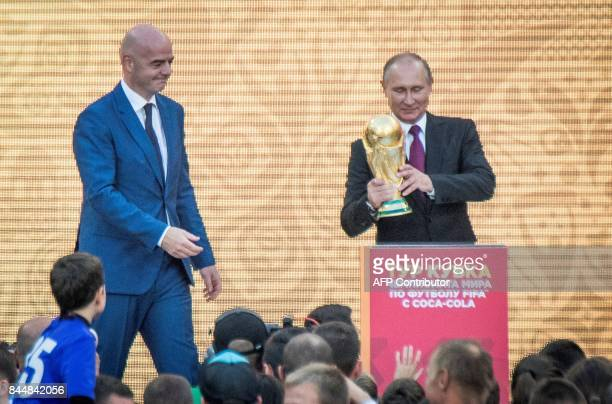 Russian President Vladimir Putin holds the FIFA World Cup Trophy flanked by FIFA President Gianni Infantino during the opening of the trophy tour...