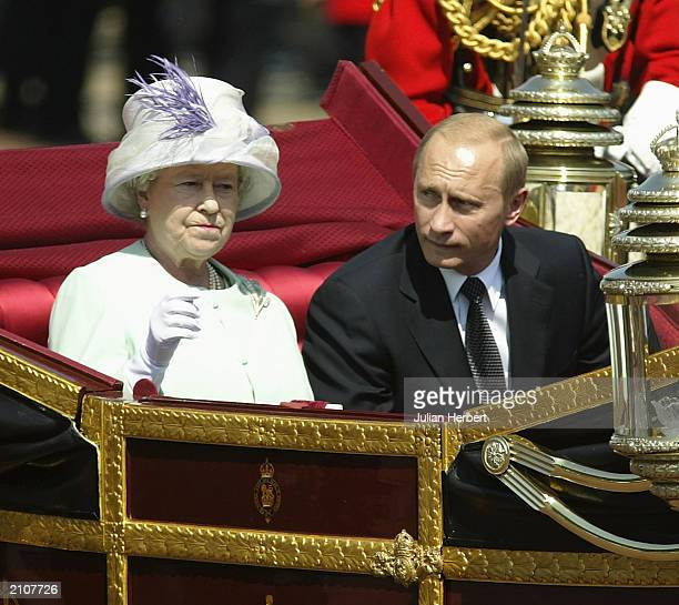Russian President Vladimir Putin is accompanied by Her Majesty The Queen during a procession at The Mallat during the start iof his state visit on...