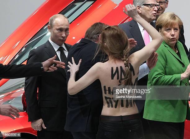 Russian President Vladimir Putin is attacked by an activist of the Ukrainian women rights group 'Femen' as German Chancellor Angela Merkel looks on...
