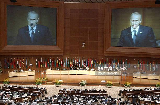 Russian President Vladimir Putin is seen on a huge screen at Putrajaya's convention center as he addresses the opening session of the 10th summit of...