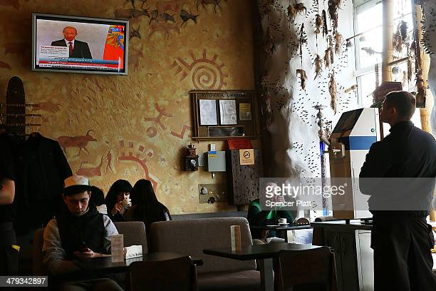 Russian President Vladimir Putin is viewed on a television screen in a cafe on March 18 2014 in Simferopol Ukraine Putin celebrated this weekend's...