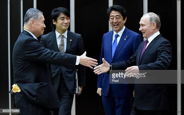 Russian President Vladimir Putin is welcomed by former Japanese Prime Minister Yoshiro Mori beside Japanese Prime Minister Shinzo Abe when he visits...