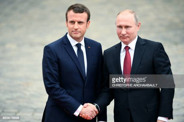 Russian President Vladimir Putin is welcomed by French President Emmanuel Macron as they shake hands at the Versailles Palace near Paris on May 29...
