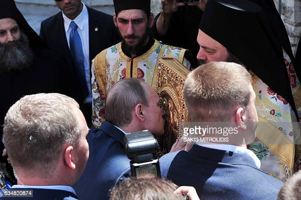 Russian President Vladimir Putin kisses a book during a visit to the monastic community of Mount Athos in Karyes on May 28 2016 Putin who has often...