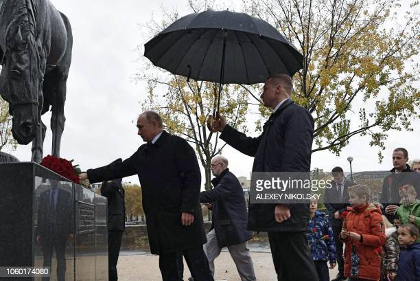 Russian President Vladimir Putin lays flowers as he attends the flowerlaying ceremony marking the centenary of the Armistice Day at the Monument to...