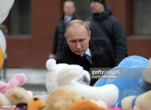 Russian President Vladimir Putin lays flowers in tribute to the victims of a fire at a shopping centre in Kemerovo on March 27 2018 At least 53...