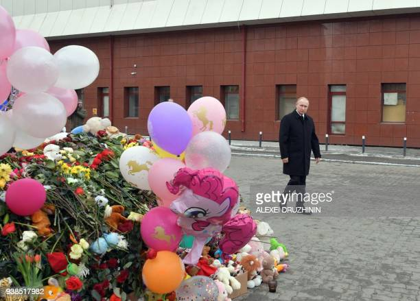 TOPSHOT Russian President Vladimir Putin lays flowers in tribute to the victims of a fire at a shopping centre in Kemerovo on March 27 2018 At least...