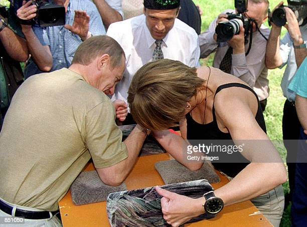 Russian President Vladimir Putin left arm wrestles with Yulia Beganova June 24 2000 near Kazan Tatarstan during celebrations for the local Sabantuy...