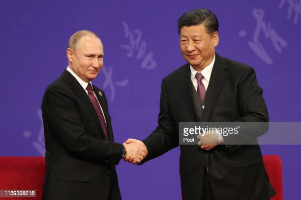 Russian President Vladimir Putin left shakes hands with Chinese President Xi Jinping right during the Tsinghua Universitys ceremony at Friendship...