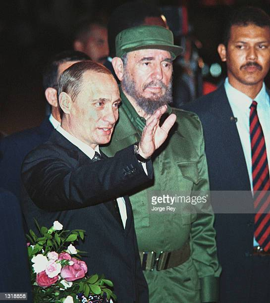 Russian President Vladimir Putin left waves during a welcoming ceremony with Cuban president Fidel Castro December 13 2000 at the Jose Marti...