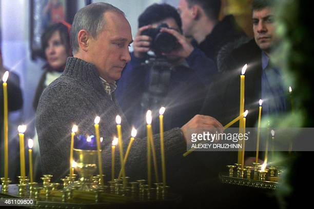 Russian President Vladimir Putin lights a candle as he takes part in an Orthodox Christmas mass in the village of Otradnoye near Voronezh early on...