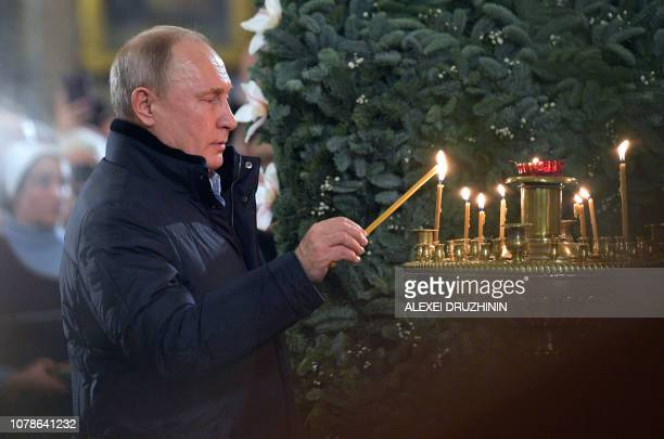 TOPSHOT Russian President Vladimir Putin lights a candle during a midnight mass at the Cathedral of the Transfiguration of the Savior of All the...