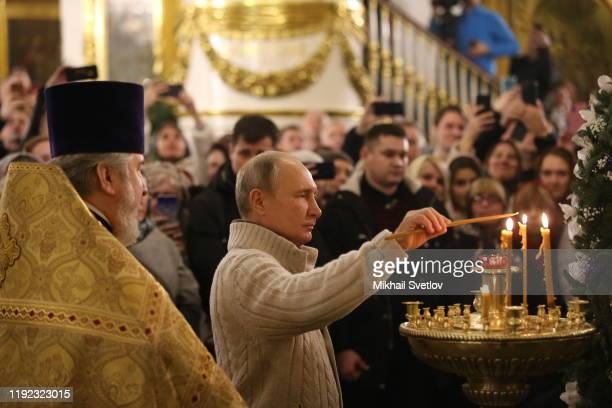 Russian President Vladimir Putin lights a candle during the Mass marking the Russian Orthodox Christmas at the Transfiguraton Cathedral January 7...