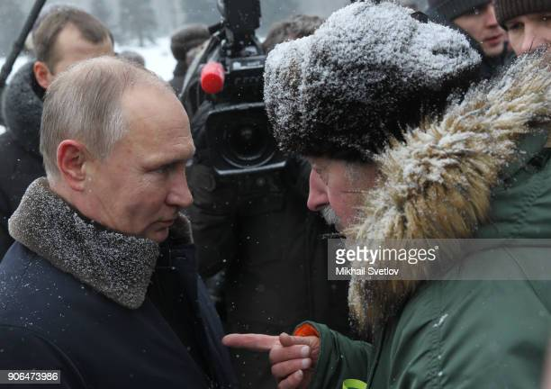 Russian President Vladimir Putin listens to a pensioner near the monuments at Piskaryovskoye cemetery in Saint Peterburg January2018 The Red Army...