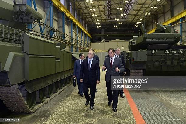 Russian President Vladimir Putin listens to Andrei Terlikov the head of the Ural Transport Machine Building Design Bureau as they walk past military...